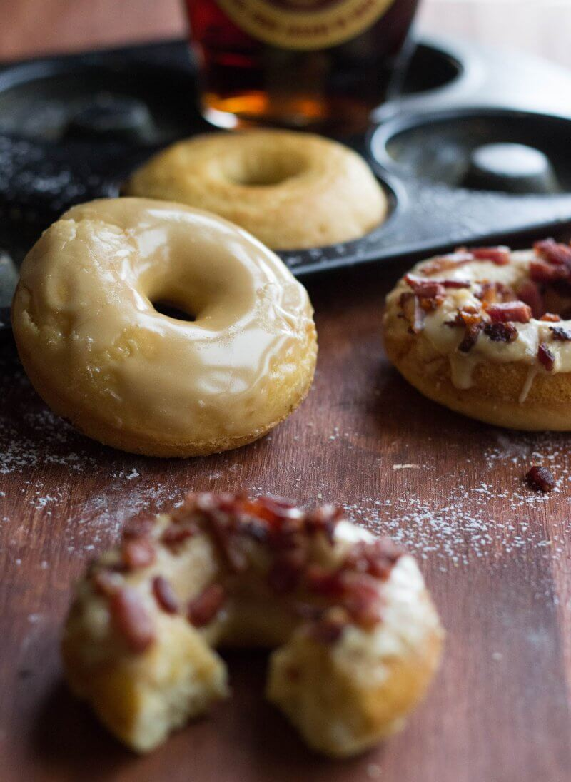 Baked Cake Maple Bacon Donuts baked in the oven, dipped into a 2 ingredient maple glaze and topped with crispy bacon pieces. | Full recipe @ FlavoursandFrosting.com