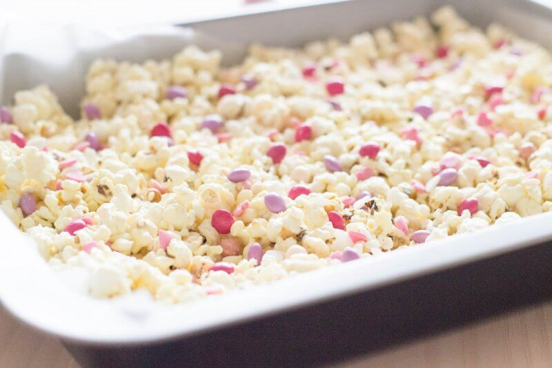 A super easy Valentines Day Gift! Valentines Popcorn made with microwave salted popcorn, melted white chocolate, mini Smarties (M&M´s will do just fine too!) and edible heart confetti | FlavoursandFrosting.com