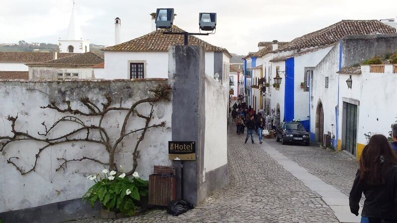 Obidos Portugal - As soon as we arrived to Obidos, I understood (as soon as I saw the castle on the hill) why people love this quaint little village so much. It'll make you feel like you are in a different time in history altogether.